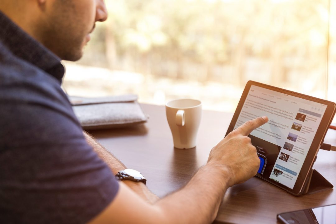 man using list on ipad at coffee bar