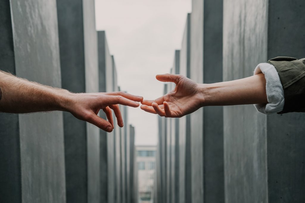 two hands meet across a gap between walls