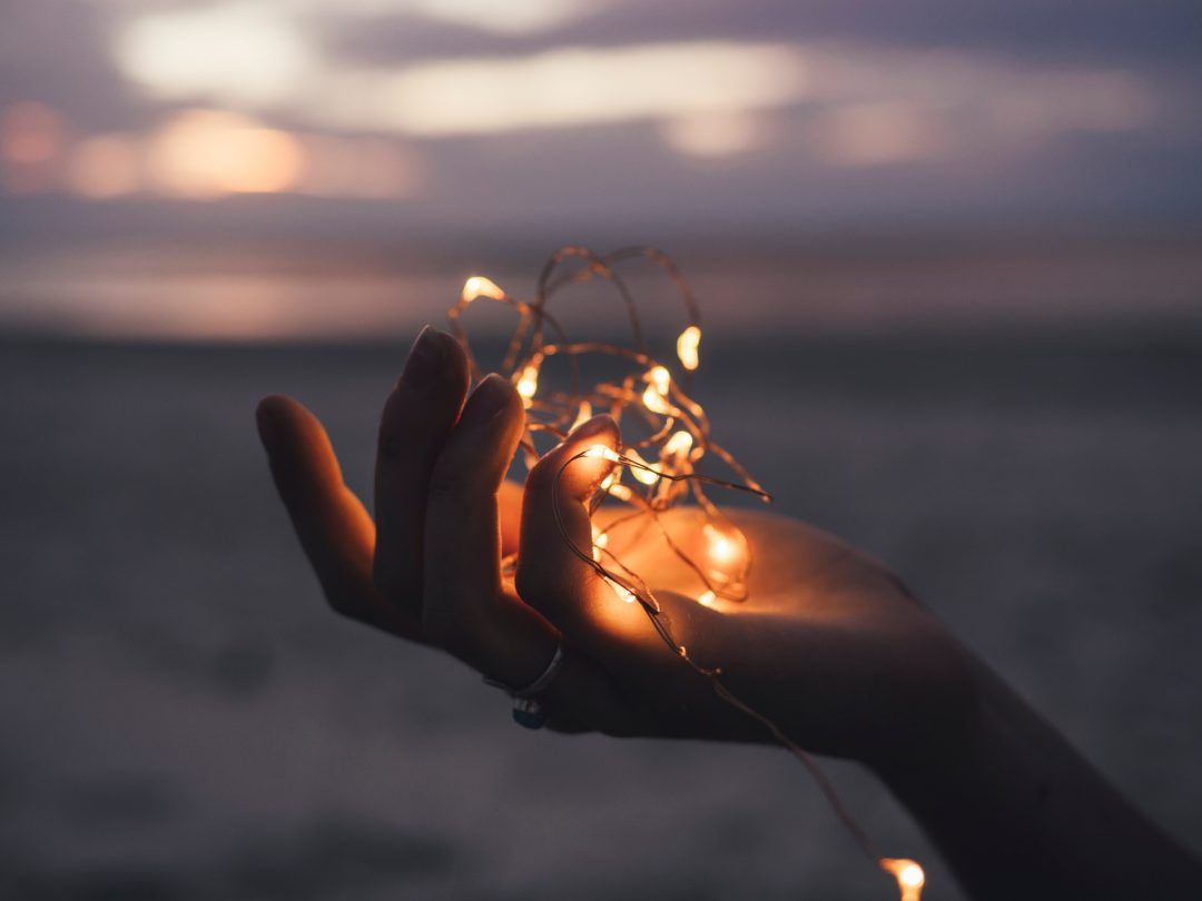 hand holding a ball of light filaments